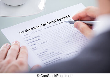 Businessperson With Pen Over Application Form