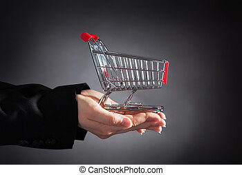 Close-up Of Businessperson Holding A Shopping Cart Over Black Background