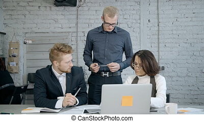 Concept of teamwork in business center. Three successful and professional businessperson working inside workplace office. Mature woman and two adult man making brainstorming research and using laptop
