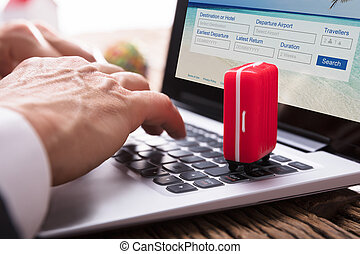Businessperson's Hand Filling The Online Vacations Packages Form