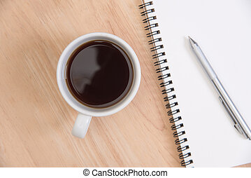Business's desk of office supplies and gadgets coffee cup, empty paper, pen on wooden table background. Top View from above.