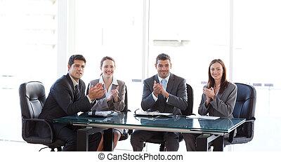 businessteam applauding during a presentation sitting around...