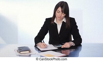 Businesswoman adding bills.