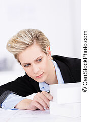 Beautiful blond businesswoman leaning sideways aligning two white blocks on her desk in the office