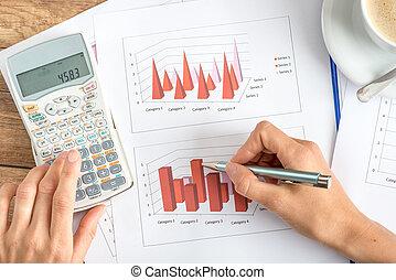 Businesswoman analysing statistical graphs
