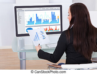 Rear view of businesswoman analyzing charts at desk in office