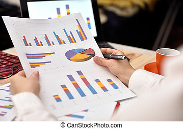 businesswoman analyzing income graphs and charts