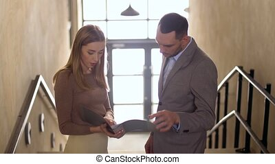 businesswoman and businessman discussing folder - business,...