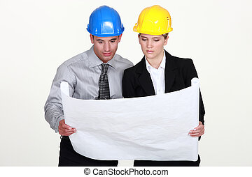 businesswoman and businessman looking at a blueprint
