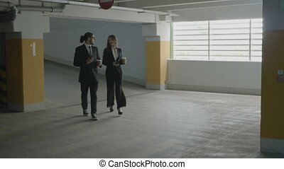 Businesswoman and businessman partners walking home after work talking while holding coffee cups and cell phones in their hands