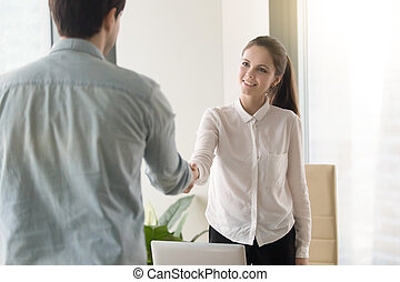 Businesswoman and businessman shaking hands, female manager gree
