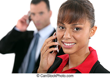 businesswoman and businessman talking on their cells