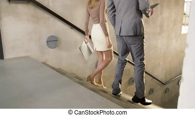 businesswoman and businessman walking downstairs - business,...