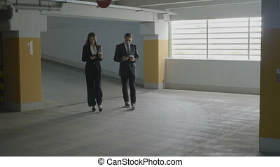 Businesswoman and businessman walking in a underground parking lot while holding coffee in their hands and looking at their smartphones