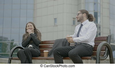 Businesswoman and businessman wearing formal suit sitting in...