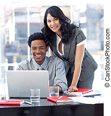 Businesswoman and businessman working with a laptop