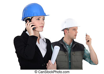 businesswoman and craftsman supervising a construction site