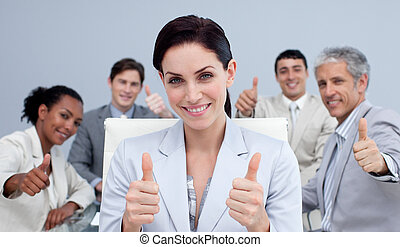 Businesswoman and her team with thumbs up in a meeting