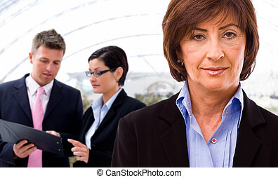Businesswoman and team - Senior businesswoman with working ...