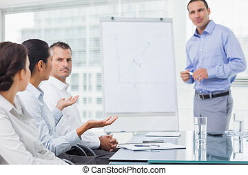 Businesswoman asking question during presentation in bright...