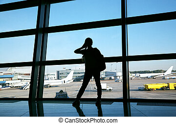 businesswoman at the airport. silhouette of a girl with mobile phone and backpack