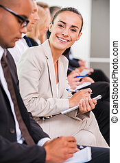Businesswoman at the conference. Side view of business people sitting in a row and writing something in their note pads while confident young woman looking at camera and smiling