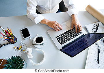 Businesswoman at the desk with laptop in her office.