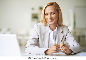 Businesswoman at workplace - Young businesswoman looking at ...