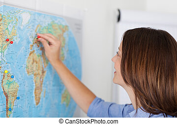 Businesswoman Attaching Pushpin On Map In Office - Closeup...