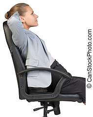 Businesswoman back in office chair with hands clasped behind her head