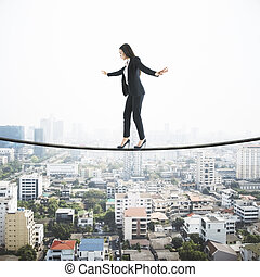 Businesswoman balancing on a string over the city, city view with scyscrapers in the background. Risk and self confidence concept