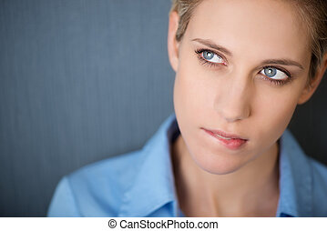 Businesswoman Biting Lip While Looking Away Against Grey Wall