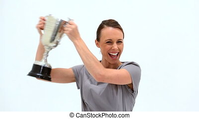 Businesswoman brandishing a trophy against white background