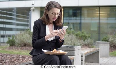 Businesswoman browsing smartphone and snacking with sandwich...