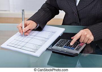Businesswoman Calculating Tax