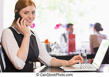 Businesswoman calling on phone and looking at camera