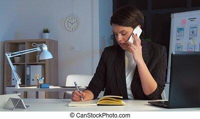 businesswoman calling on smartphone at dark office -...