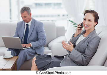 Businesswoman calling while her colleague working on his laptop