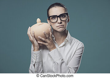 Businesswoman shaking a money box and checking her savings, deposit and investments concept