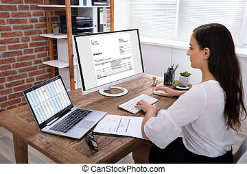Businesswoman Checking Invoice On Computer