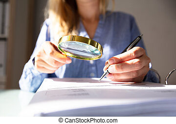 Businesswoman Checking Invoice With Magnifying Glass