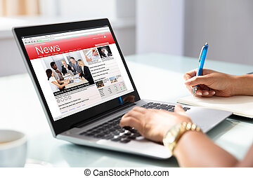 Businesswoman Checking Online News On Laptop