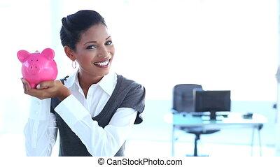 Businesswoman checking piggy bank