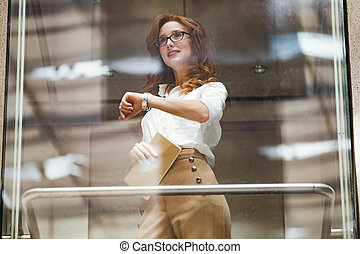 Businesswoman checking watch while standing in elevator