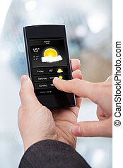 Businesswoman Checking Weather Forecast On Smartphone