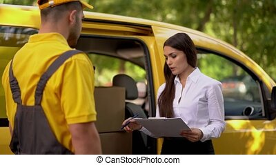 Businesswoman checks delivery from courier in yellow uniform outdoor near his car
