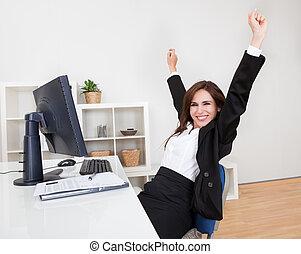 Businesswoman Cheering At Desk - Portrait of Cheering...
