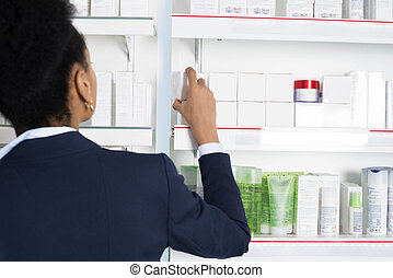 Businesswoman Choosing Medicine In Pharmacy