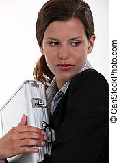 Businesswoman clutching metal briefcase