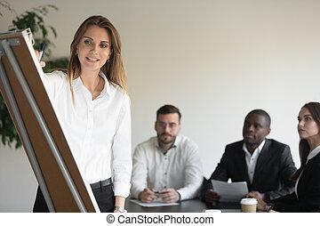 Businesswoman coach speaker drawing on flip chart giving business presentation
